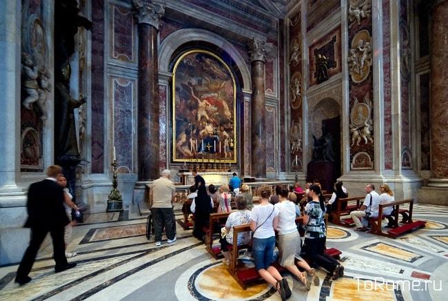 Молящиеся туристы в соборе